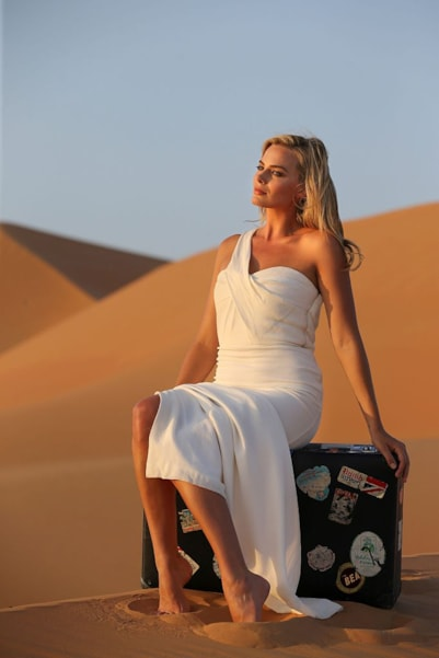 ABU DHABI, UNITED ARAB EMIRATES - NOVEMBER 05:  Australian actress Margot Robbie exudes vintage Hollywood glamour in Abu Dhabi's Liwa Desert during a visit to celebrate the launch of the new British Airways Boeing 787-9 Dreamliner's daily London-Abu Dhabi-Muscat service on November 5, 2015 in Abu Dhabi, United Arab Emirates. Margot is wearing a beautiful gown from Burberry's Prorsum collection. (Photo by Wouter Kingma/Getty Images for British Airways)
