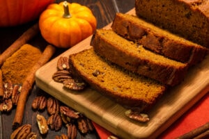 Pumpkin,Bread,Loaf,Sitting,On,Wooden,Cutting,Board,With,Pecan